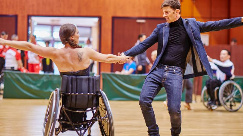 Woman wheelchair dancer and her standing partner perform